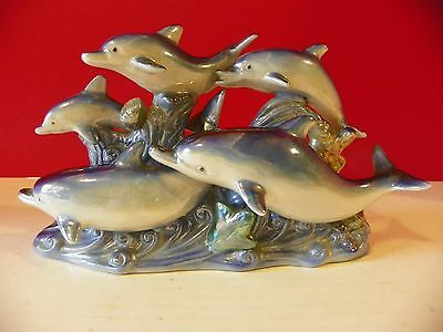 Ceramic cluster of five dolphins riding the waves