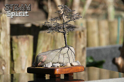 Black copper tree handmade wire sculpture on natural rock
