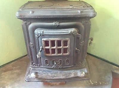 Antique vintage cast iron parlor stove, old wood burning stove with windows