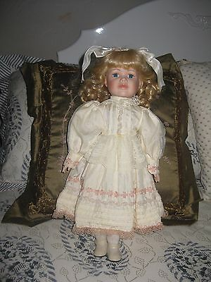 Porcelain doll .Cream dress with lace highlights. Excellent condition.