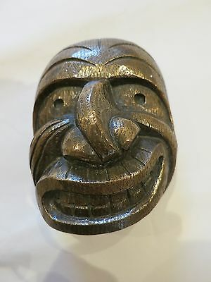 A vintage solid bronze? ethnic wall mask with bared teeth