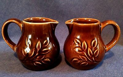 Holkham Pottery. Two small brown jugs.