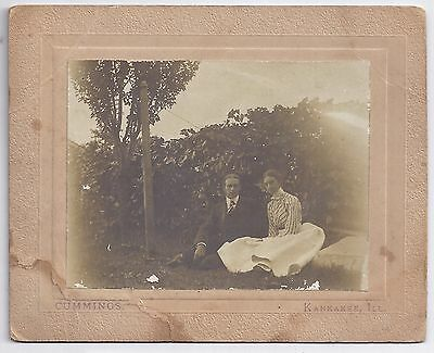 Young couple sitting on grass - by Cummings, Kankakee, IL