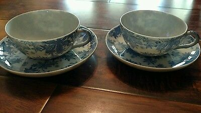 pair of blue and white tea cups and saucer