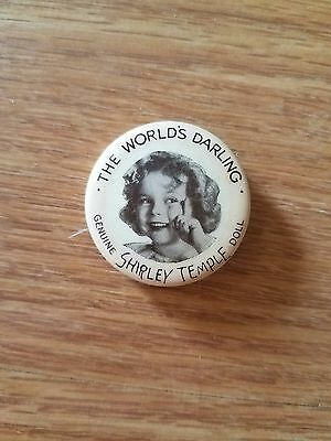 """1930s Shirley Temple pin stating """"THE WORLD'S DARLING GENUINE SHIRLEY TEMPLE..."""