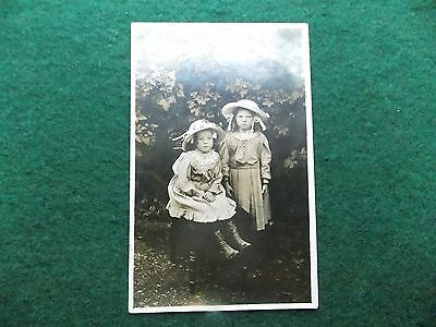 Two Beautifully Dressed Young Girls with Big Hats in Garden Vintage RP Postcard