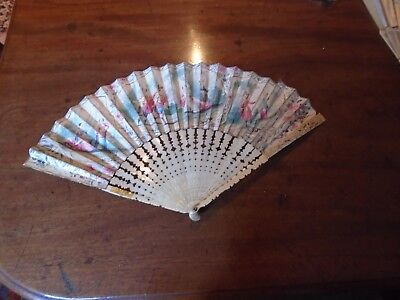 Antique fan with intricately carved sticks and painted leaf
