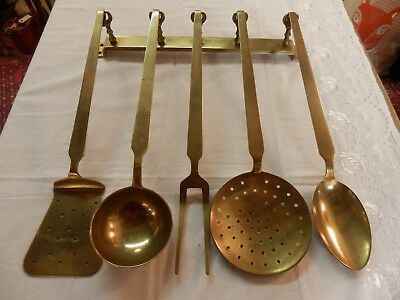 A very beautiful French vintage set of heavy brass kitchen utensils with hanger