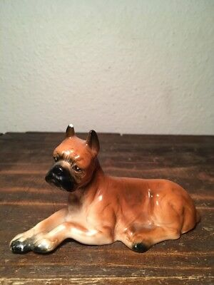 Vintage ceramic boxer dog lying down figurine with a sad face.