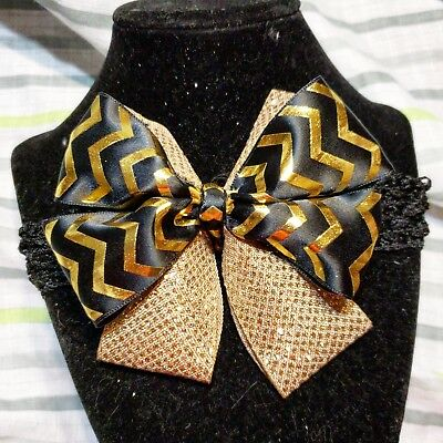 black and gold baby girls head band with a large bow and gold sparkles