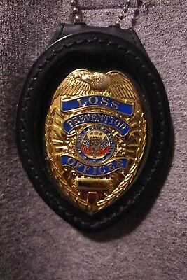 Gold loss prevention badge with leather law enforcement chain badge holder.