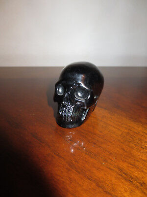 Carved obsidian stone skull statue