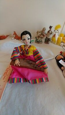 Asian Doll Playing a Wooden Instrument