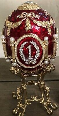 """Red enamel on guilloche-treated metal egg, 6.8"""" on stand, four portraits, flawed"""