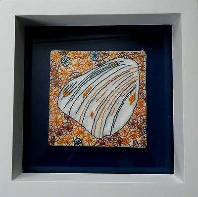 Framed Embroideries of shell fragments, white Habitat frame blue orange brown