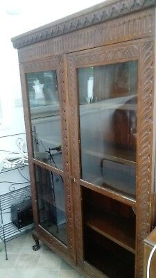 Carved oak bookcase with glass doors and adjustable shelves