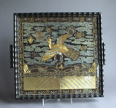 A Chinese late C19th silk male peacock rank badge, glazed and mounted as a tray