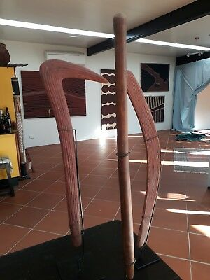 2 Aboriginal boomerangs and a nulla nulla mounted on metal stands