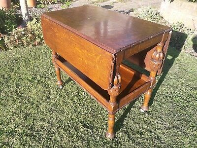 Drop leaf trolley table with carved legs and wheels.