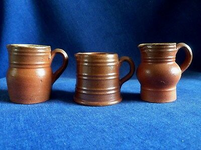 A collection of three small vintage brown jugs.