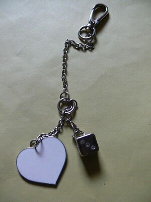 A Long, Silver Tone Bag Charm With White Heart & Silver Tone Dice.