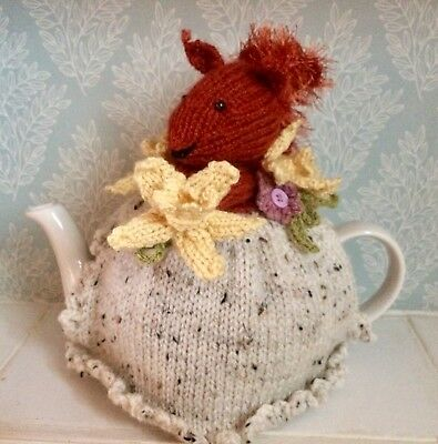 hand knitted tea cosy with  a squirrel, daffodils and crochet flowers