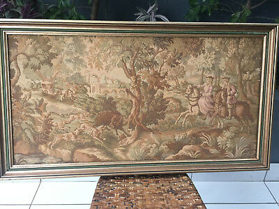 Framed tapestry of a hunting scene featuring hunters, dogs and wild boar.