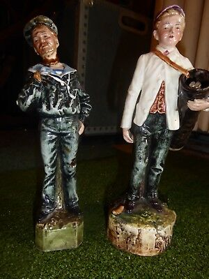 Two figurine statues of golfer and sailor