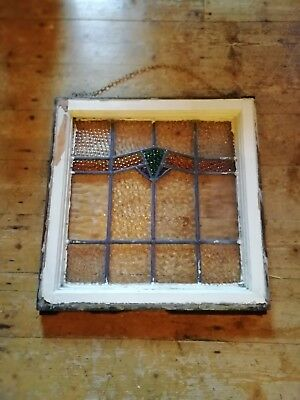 Old piece of stained glass in original wood frame with chain to hang