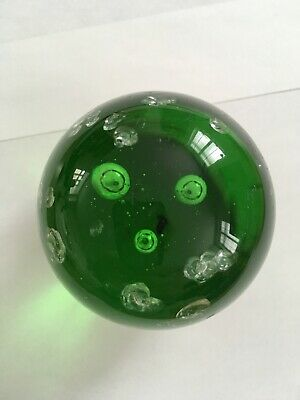 Green, round paperweight with bubbles and marks inside. Small piece of label.