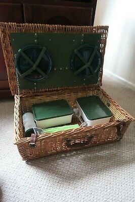 vintage wicker picnic basket with leather straps and a few cutlery items