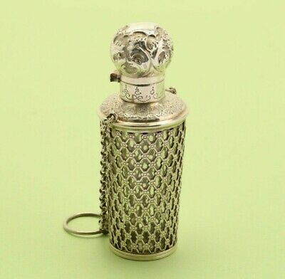 A late 19th century French silver and glass scent bottle on chain, circa 1880