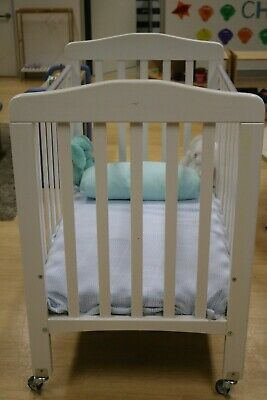 White wooden cot with wheels