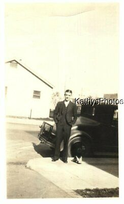 Found B&W Photo H_2051 Man Standing In Front Of A Car, Shoes On The Sidewalk