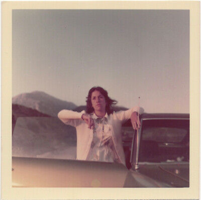 Woman leaning on open car door, mountain setting, 1970s