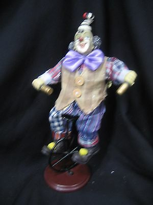 clown figurine on metal unicycle cloth with plastic head hands shoes