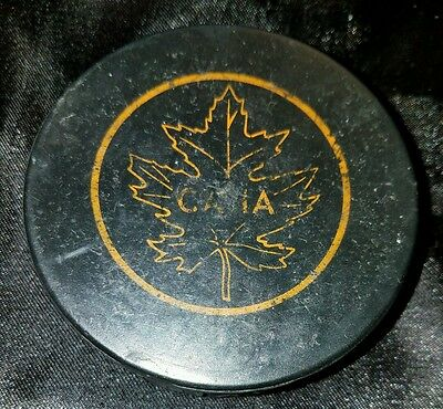 old vintage leaf hockey puck with hole in the back