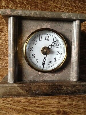 Small clockwork mantel clock in a marble surround Battery