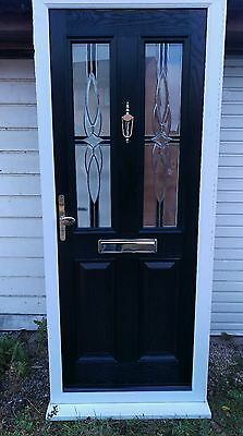 Black composite door with white upvc frame and cill.