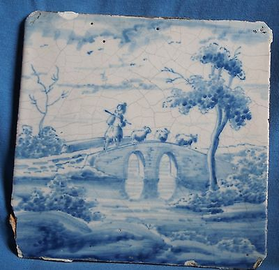 Blue and white antique Delft tile with pastoral scene with a shepherd on bridge