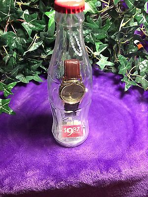 2002 Coca Cola LEATHER STRAP WRIST WATCH IN A PLASTIC BOTTLE