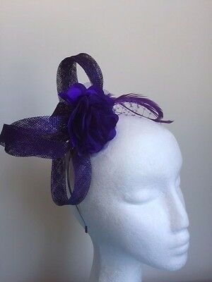 Cute purple loop fascinator with flower, netting and feathers on headband.