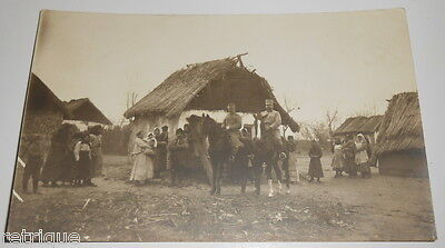 Old Postcard, Military on Horse Back In Village Of Poorly Built Homes or Huts.