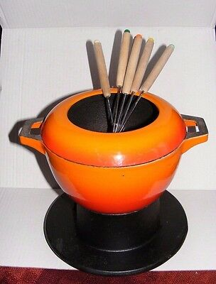 fondue,cast iron and flame orange on stand with forks
