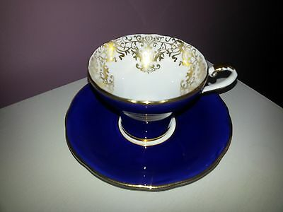 aynsley cobalt blue cup and saucer with gold pattern.