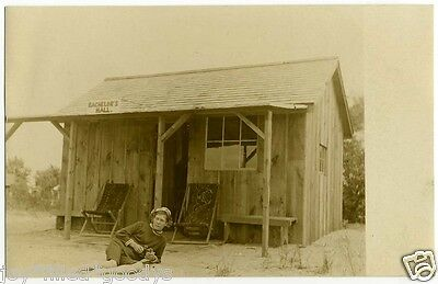 1900s MAN IN SWIMSUIT WITH BINOCULARS LAYING IN FRONT OF HIS CABIN REAL PHOTO PC