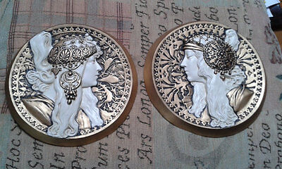 A pair of mucha style cameo wall plaques in cream/gold