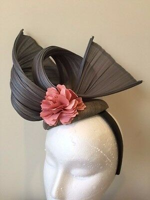 Grey ginsin fascinator with a pink satin flower on a black headband. Stunning on