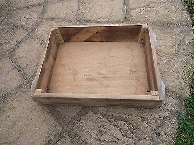 Wooden storage drawer on wheels, used regularly in workshop.