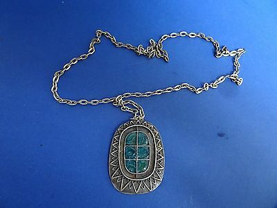 Arts and Crafts style pendant on a chain.